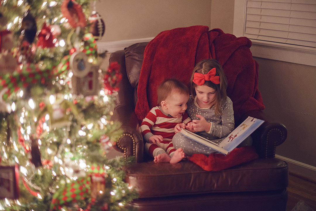 Children reading a book at Christmas time while sitting next to a Chrstmas tree | St. Louis Mini Session Photographer | Fresh Art Photography | Jodie Allen